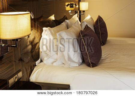 Cushions and dressed bed linen on the bed in the hotel