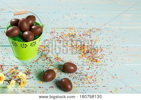 Beautiful Easter Composition With Chocolate Eggs In The Iron Pail, Colored Powder For Cakes And Flow