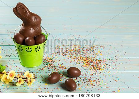 Beautiful Easter Composition With Chocolate Bunny And Eggs In The Iron Pail, Colored Powder For Cake