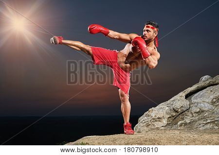 Horizontal full length shot of a kickboxing fighter training outdoors at night strength power agility energy endurance muscles abs toning fit fitness sports sportsperson combat martial confidence.