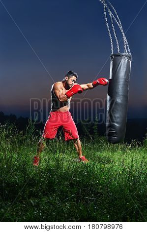 Vertical shot of a shirtless boxer with strong ripped muscular body punching a sandbag training outdoors at night sports motivation lifestyle people sportsman athletics fitness muscles strengthening .