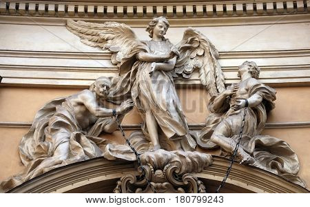 ROME, ITALY - SEPTEMBER 05: Statue of Angel about to free two slaves joined at the wrists by a real iron chain on facade of Santissima Trinita degli Spagnoli Church in Rome, on September 05, 2016.