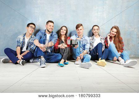 Happy friends taking selfie while sitting on floor indoors