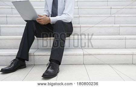 Low section of young businessman using laptop on office steps
