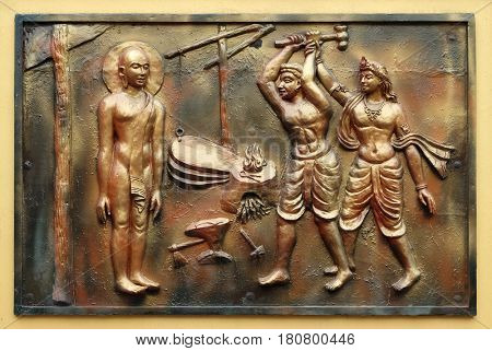 KOLKATA,INDIA - FEBRUARY 09, 2016: Indra prevents an ignorant cowherd from assaulting Bhagavan Mahavira, bass relief on the wall of Jain Temple (also called Parshwanath Temple) in Kolkata, India