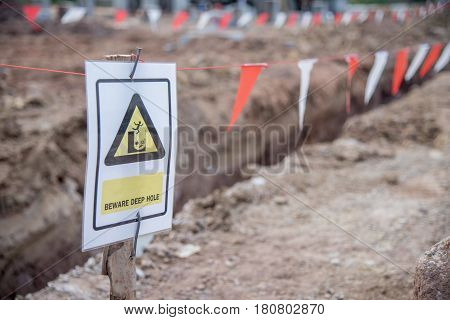 Beware deep hole warning sign and white red flag safety in construction site