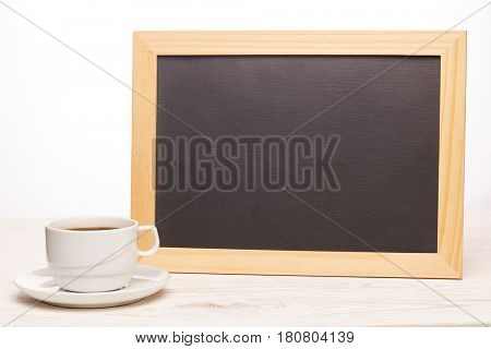 Black board with blank space for text  and cup of coffee on a wooden table on a white background. Copy space for adding your content. Menu. Advertising