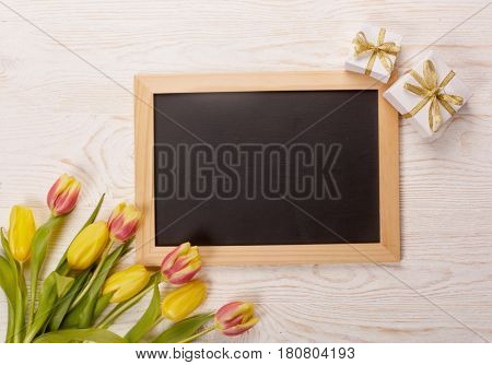 Black board with blank space for text, bouquet of tulips and gift boxes on a wooden background. Top view with copy space. Greeting card. Advertising.