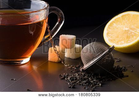 cup of tea with a strainer and a lemon on a dark background.