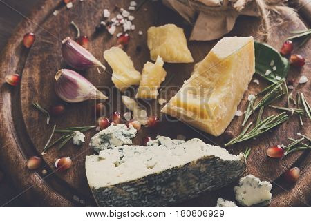 Cheese delikatessen platter closeup on wood. Wooden desk with blue cheese roquefort, parmesan, camembert and brie cuts decorated with garlic, pomegranate and rosemary. Filtered