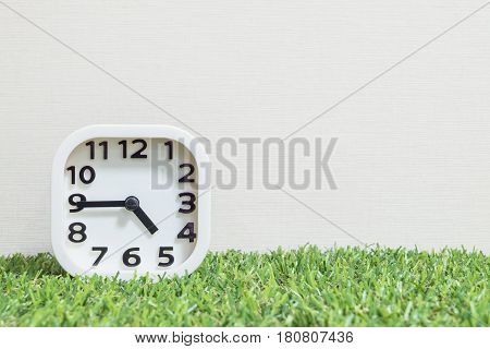 Closeup white clock for decorate show a quarter to five o'clock or 4:45 p.m. on green artificial grass floor and cream wallpaper textured background with copy space