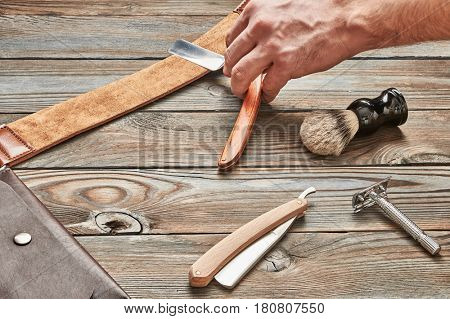 Man stropping straight razor with leather tool against old wooden background