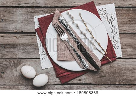 Top View Of Easter Table Setting With Cutlery, Catkins And Easter Eggs On Wooden Table, Happy Easter