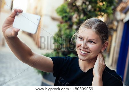 Happy smiling female tourist walking on european street and taking selfie. Concept of modern lifestyle and travel.
