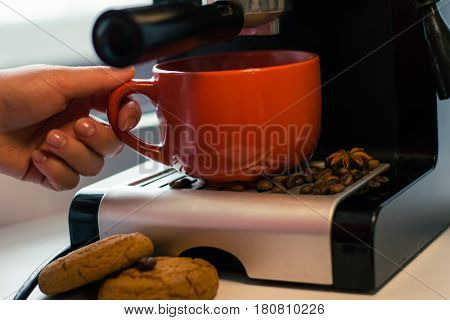 Girl make fresh coffee in a coffee machine with flavoring
