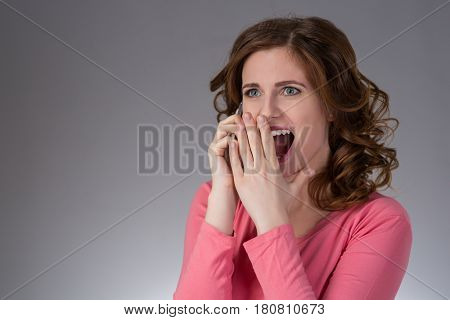beautiful young woman  in a pink shirt expresses emotions with smartphone pushes his finger and smiling on a gray background