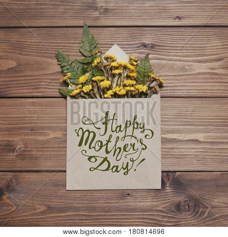 Happy Mother's day! Yellow coltsfoot flowers in envelope on brown wooden background