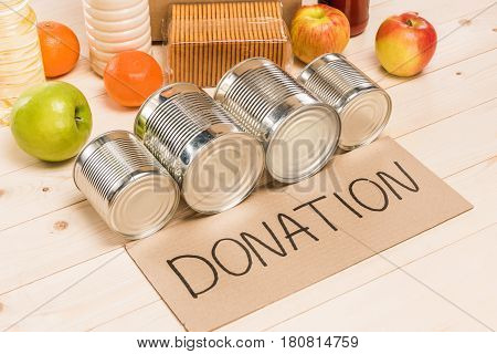 Different Food With Cardboard Donation Sign On Wooden Table, Donation Concept