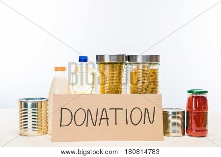 Different Food With Cardboard Donation Sign On Wooden Table On White, Donation Concept