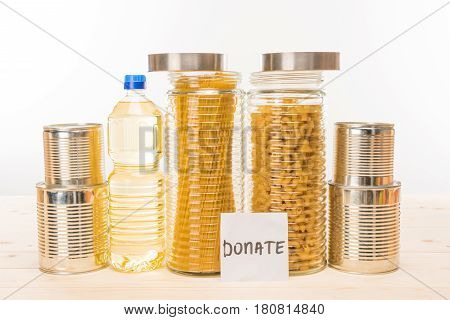 Different Food And Paper Note With Word Donation On Wooden Table On White, Donation Concept