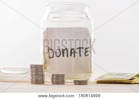 Close-up view of dollar banknotes in glass jar and stacked coins donation concept