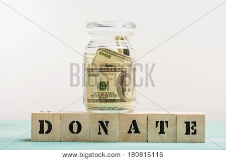 Dollar banknotes in glass jar and wooden cubes with donate lettering donation concept