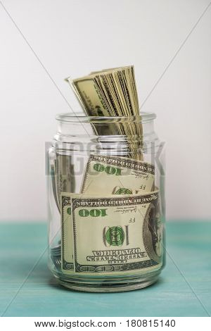 Close-up view of dollar banknotes in glass jar donation concept