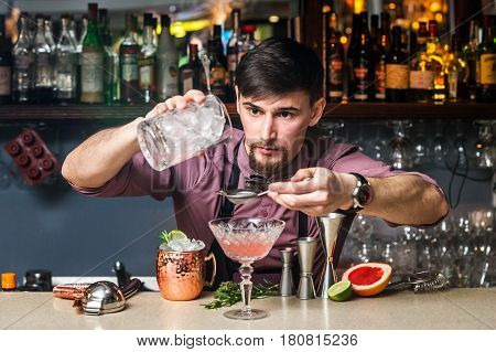 Serious and professional barman prepares drinks in the club behind the bar