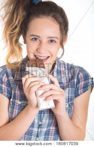 Young girl in a plaid shirt on isolated background showing her dental braces and bites the chocolate