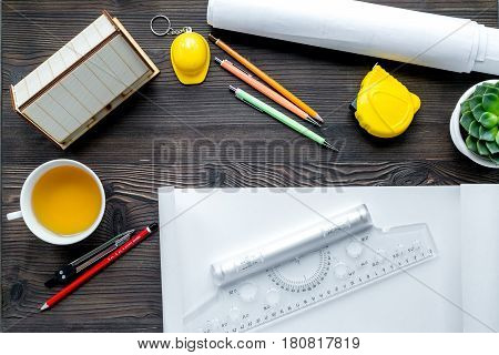 Architects workplace with constructor tools with cup of tea and projects on wooden table background top view