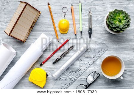 Architects workplace with constructor tools with cup of tea and projects on light wooden table background top view