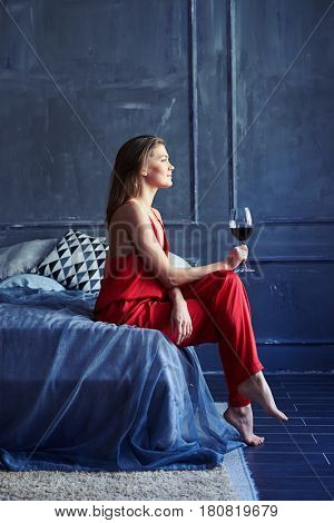 Side view of an attractive woman relaxing in bed enjoying glass of wine. Young girl sitting on the bed and looking at the window