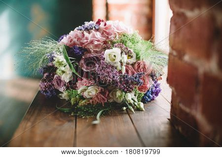 Tenderless bouquet with bow and ribbons in green and pink and blue colours on brown background