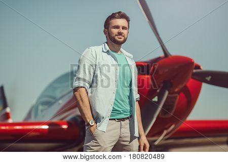 Pilot and airplane. Cheerful handsome young man pilot standing near small sport plane