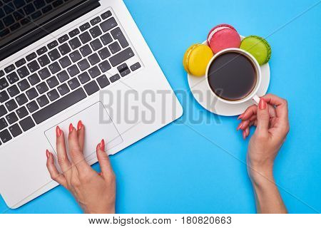 Cropped hands using touchpad and holding a cup of coffee with macaroons