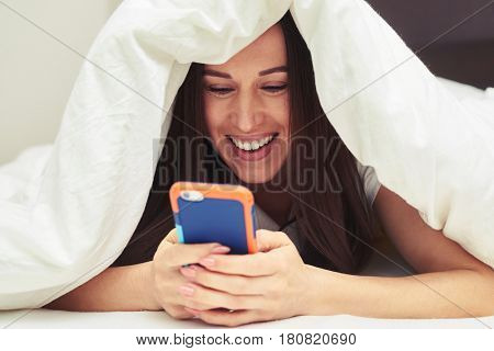 Close-up shot of a delicate female hiding under the blanket with mobile phone. Cheerful young girl lying under blanket and typing on mobile phone in bed