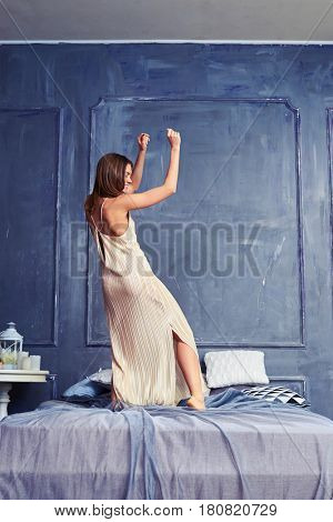 Back view of a woman dancing with raised hands on the bed. Elated female having fun early in the morning. Woman wearing a long nightgown standing on the bed
