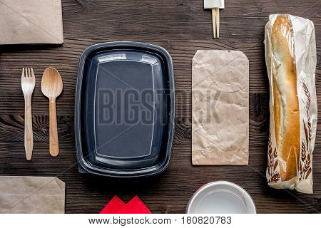 food delivery service workdesk with paper bags and sandwich on wooden background top view