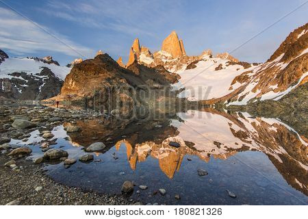 towers of Fitz Roy mountain and lake lago de los tres at red sunrise with man far away