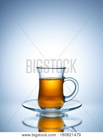 Tea in glass cup on bright background
