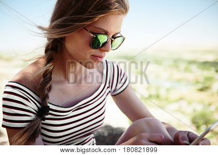 Young business woman checking e-mail and typing response outside on sunny day. Concept of mobility and technology.