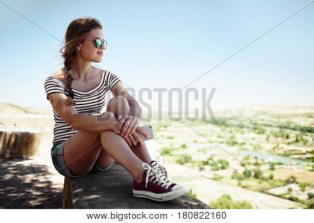Pretty woman in casual outfit sitting on stone looking at beautiful scene of countryside. Young teenage girl meditating or relaxing alone in silence.