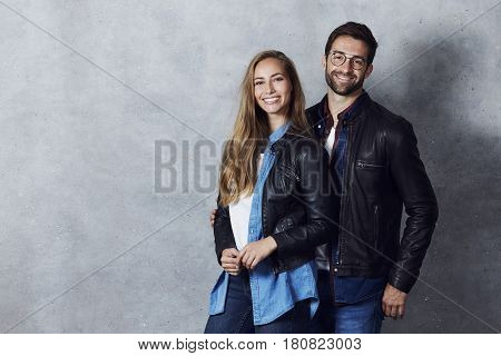 Leather jacket couple smiling at camera studio