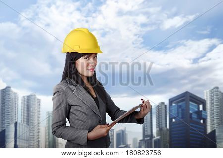 Smiling asian contractor woman with yellow helmet holding clipboard against skyscraper background