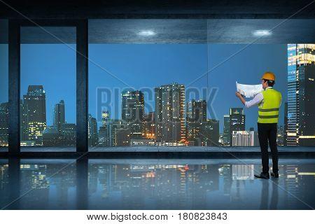 Young Asian Engineer Man Looking At His Blueprints At Room