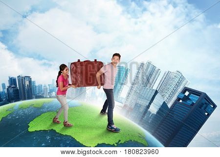 Happy asian couple carrying big suitcase going to travelling on top of the earth