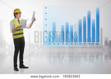 Professional Asian Contractor Man Holding Paper With Financial Charts