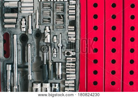 A set of accessories for the tightening of bolts lying on the background of metal constructions of red color