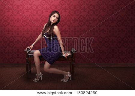 Sexy asian woman with purple dress sitting in sofa at indoor background