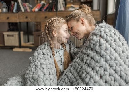 Beautiful Happy Mother And Daughter Sitting Together Under Merino Wool Blanket